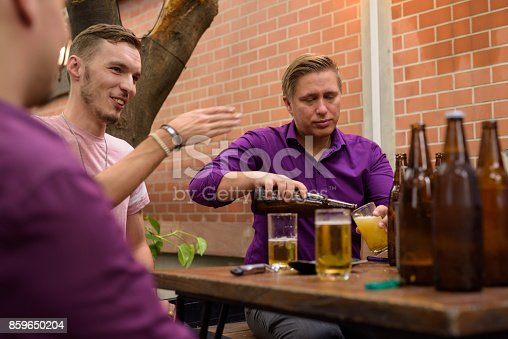 Group of Finnish men hanging out and relaxing together in the backyard at home horizontal shot
