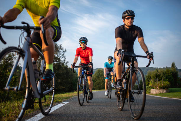 Group of Fit Cyclists Riding Mountain Road in Morning stock photo
