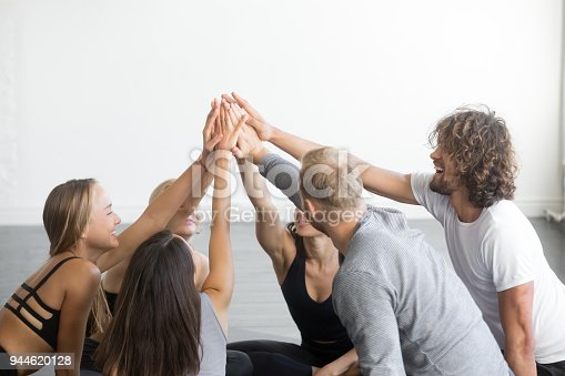 670054434istockphoto Group of fit happy people giving high five 944620128