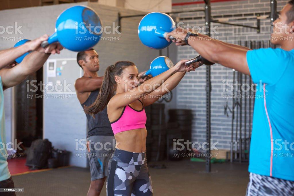 Gruppe von Fit starken Menschen in der Turnhalle dabei Kettle Bell Training mit Instruktor – Foto