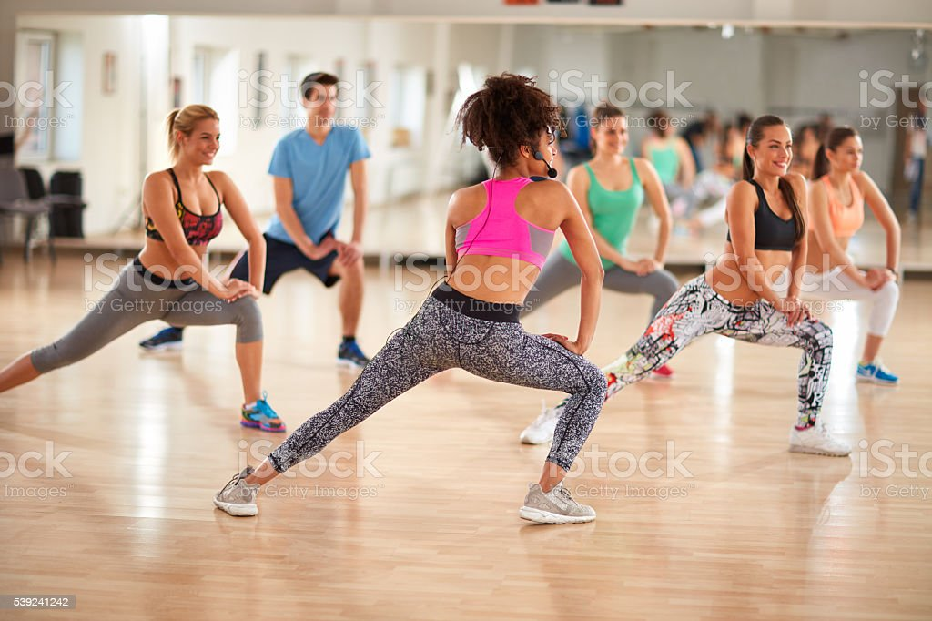 Group of fitness exercisers in colorful sports clothes in fitnes royalty-free stock photo