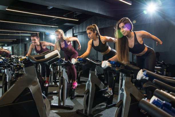 gruppe von fitness mädchen reiten heimtrainer zusammen auf radfahren klasse am gym. - kinder die schnell arbeiten stock-fotos und bilder
