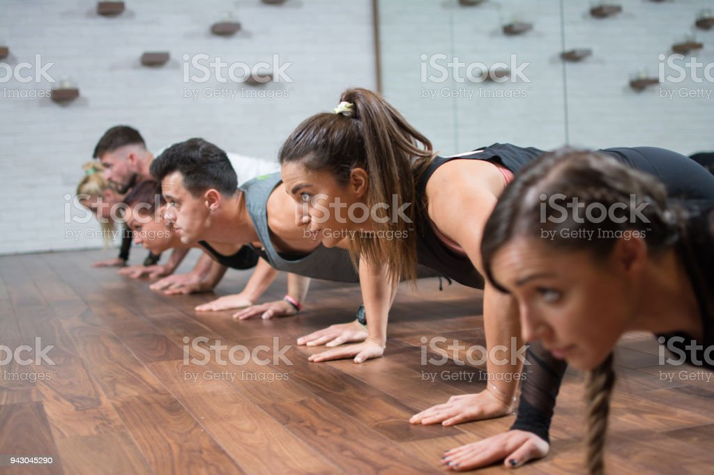 Group of fitness people doing push ups in gym stock photo