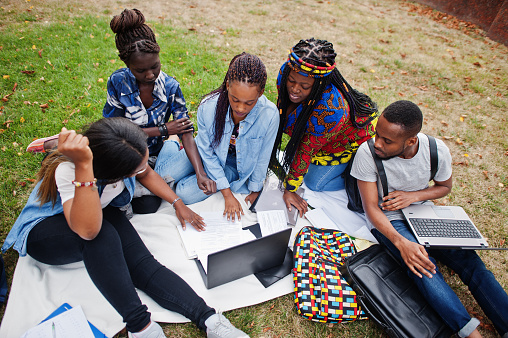 Group of five african college students spending time together on campus at university yard. Black afro friends sitting on grass and studying with laptops.