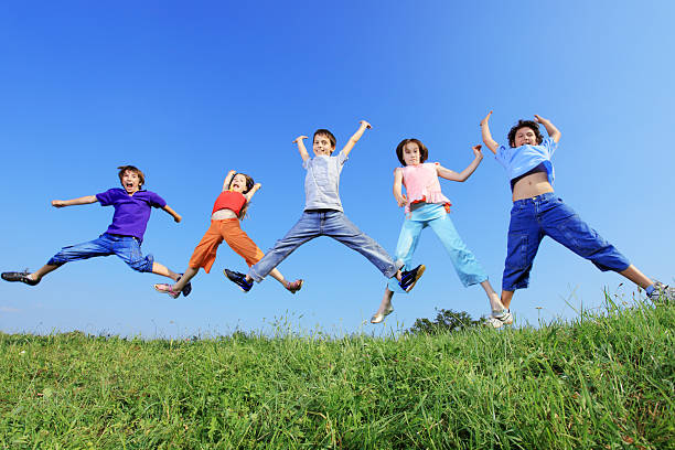 5fc6e76af9902 Group Of Five Children Jumping Outdoors Stock Photo   More Pictures of  Agricultural Field