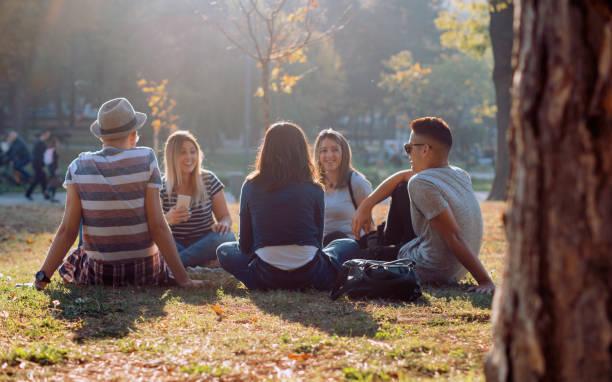 grupa pięciu przyjaciół śmieje się głośno na świeżym powietrzu, dzieląc dobry i pozytywny nastrój - wypoczynek zdjęcia i obrazy z banku zdjęć