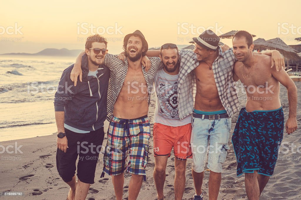 group of five friends walking on the beach stock photo