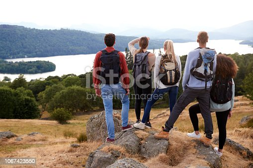 istock A group of five mixed race young adult friends admire the view after arriving at summit after a mountain hike, back view, close up 1067423550