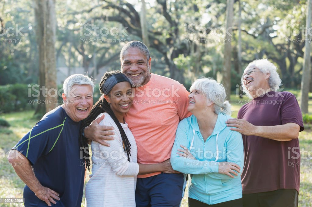 Group of five multi-ethnic seniors standing in park stock photo