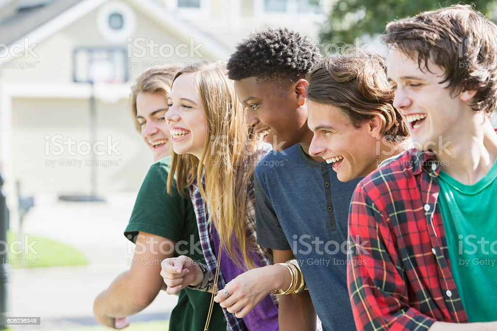 Group of five multi-ethnic teenagers hanging out stock photo