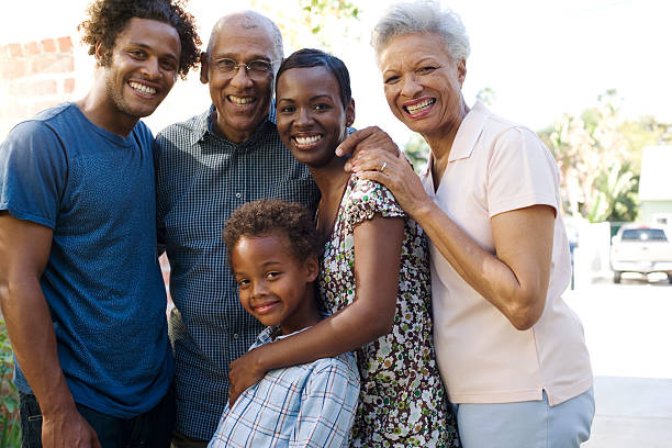 Group of five people in front of house stock photo