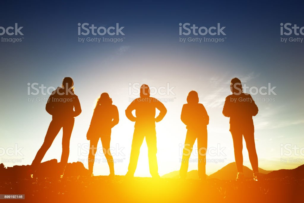 Group of five peoples in silhouettes at sunset royalty-free stock photo