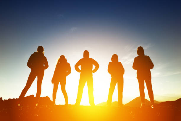 Group of five peoples in silhouettes at sunset - foto stock