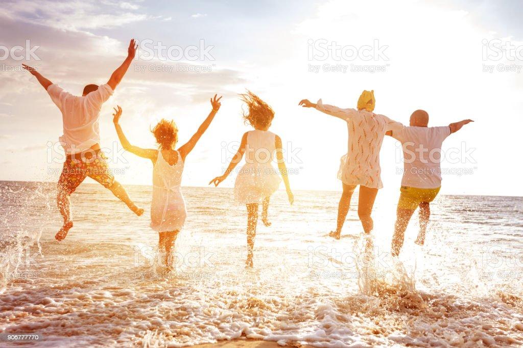 Grupo de cinco pueblos, correr y saltar al mar al atardecer - foto de stock