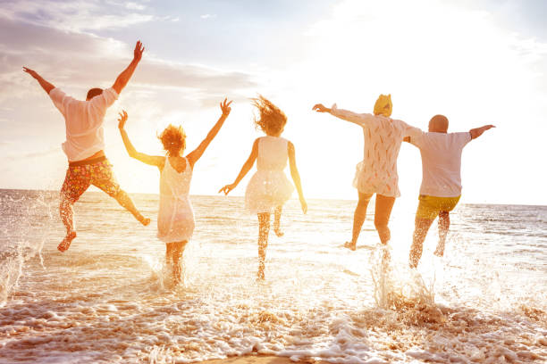 Group of five peoples run and jump to sunset sea stock photo