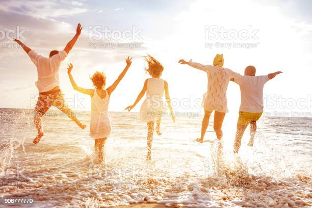 Photo of Group of five peoples run and jump to sunset sea