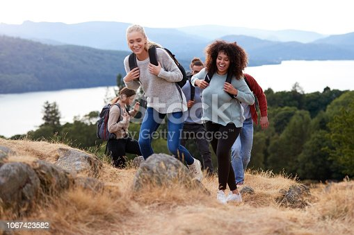 1051098428istockphoto A group of five young adult friends smiling while hiking together to a mountain summit 1067423582