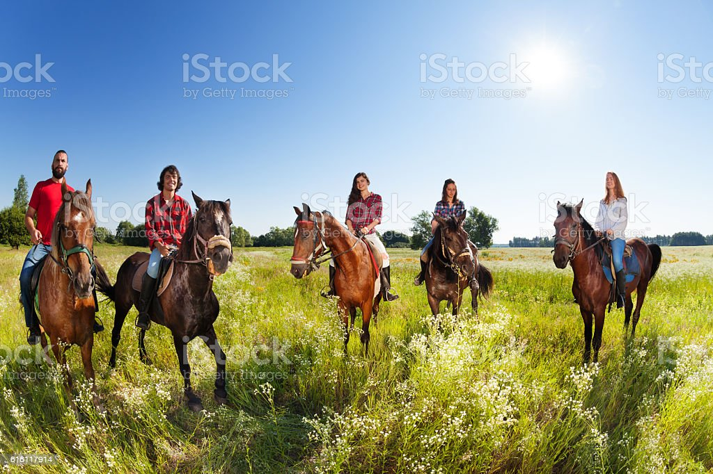 Group of five young people enjoy riding horses stock photo