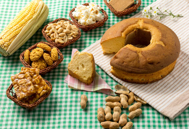 Group of food of Festa Junina, a typical brazilian party: Pe de moleque, peanut, cake, corn, cookies, porcorn. Green Table. stock photo