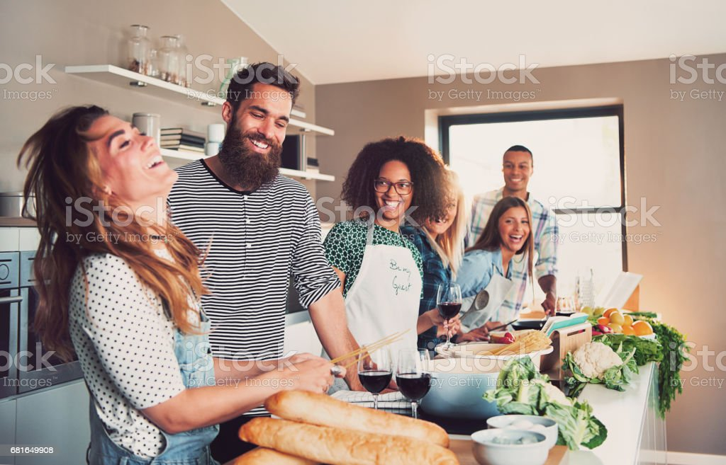 Group of foodies preparing a meal together stock photo