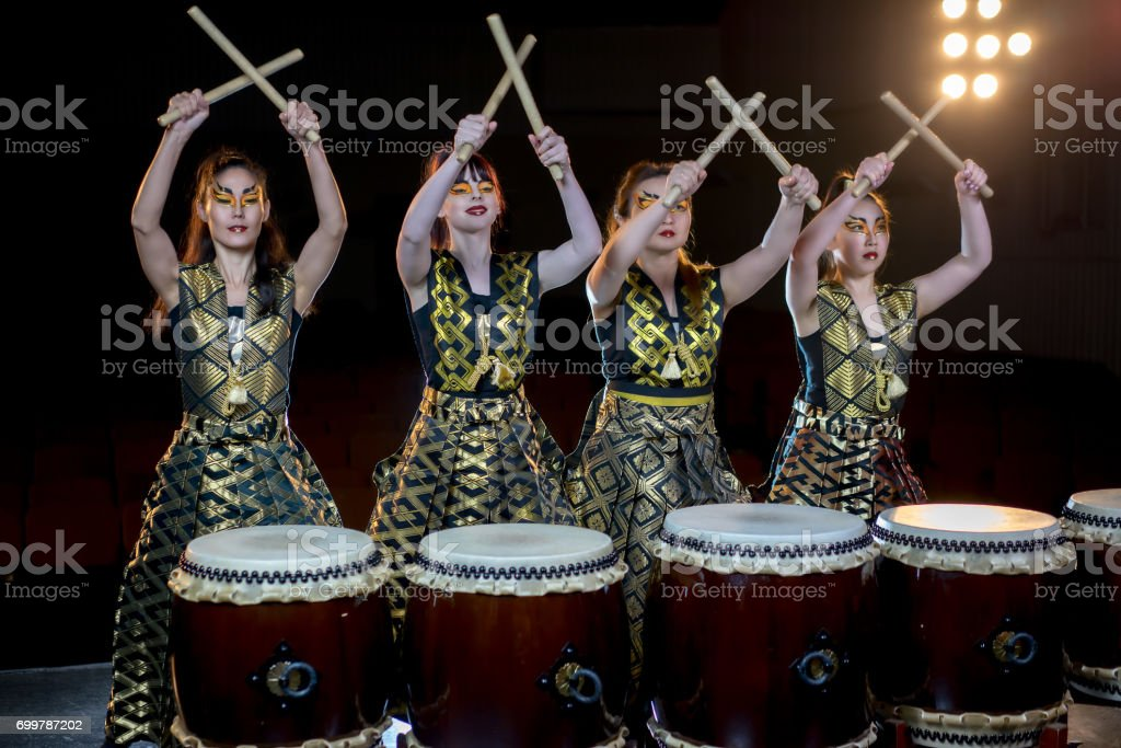 group of four beautiful asian drummer girls with drumsticks, concert studio shot on a dark background. stock photo