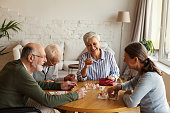 istock Group of four cheerful senior people, two men and two women, having fun sitting at table and playing bingo game in nursing home 1286546794