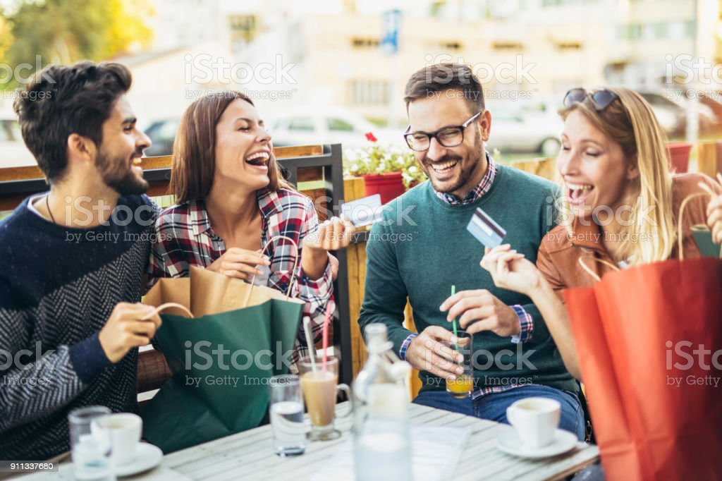 Group of four friends having fun a coffee together after shopping stock photo