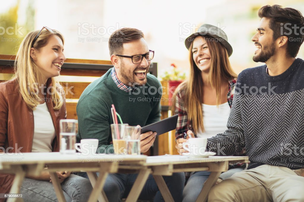 Group of four friends having fun a coffee together stock photo