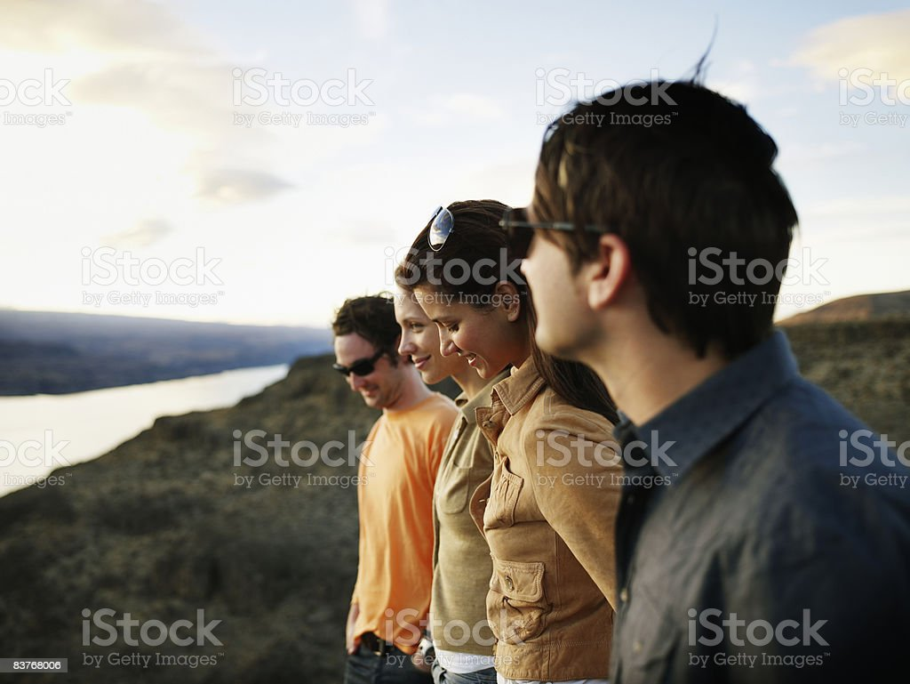 Group of four friends standing watching sunset royalty-free stock photo
