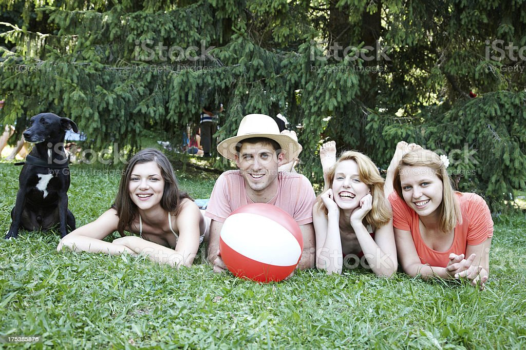 Group of four friends with dog in park royalty-free stock photo