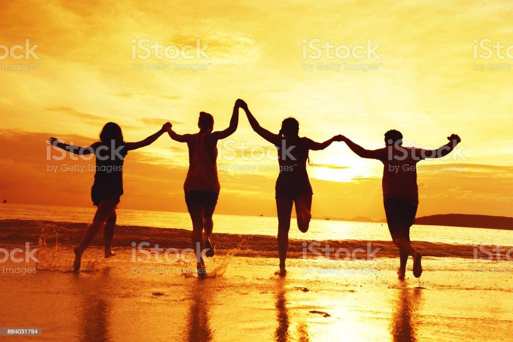 Grupo de cuatro amigos felices en la playa al atardecer - foto de stock