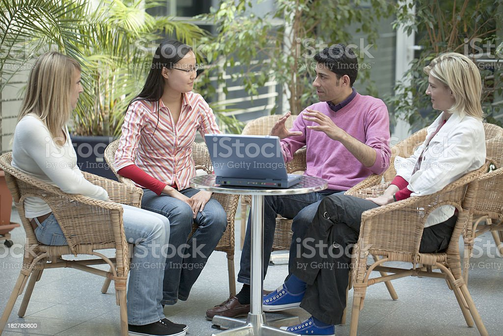 Group of four multi-ethnic students in discussion with laptop presentation royalty-free stock photo