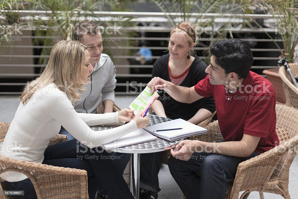 Group of four multi-ethnic students in teamwork royalty-free stock photo