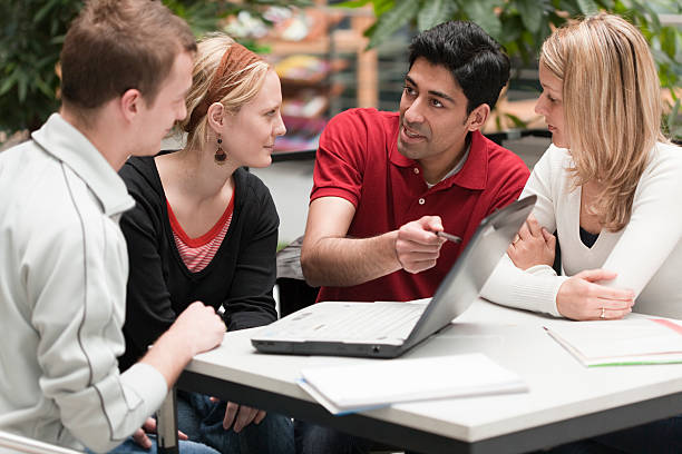 Group of four multi-ethnic students in teamwork with laptop presentation stock photo