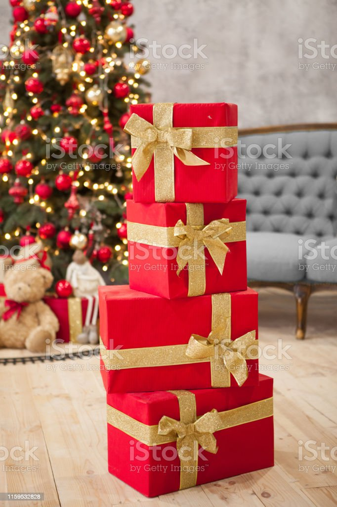 Group of four red gift boxes with gold ribbons bows standing on each...