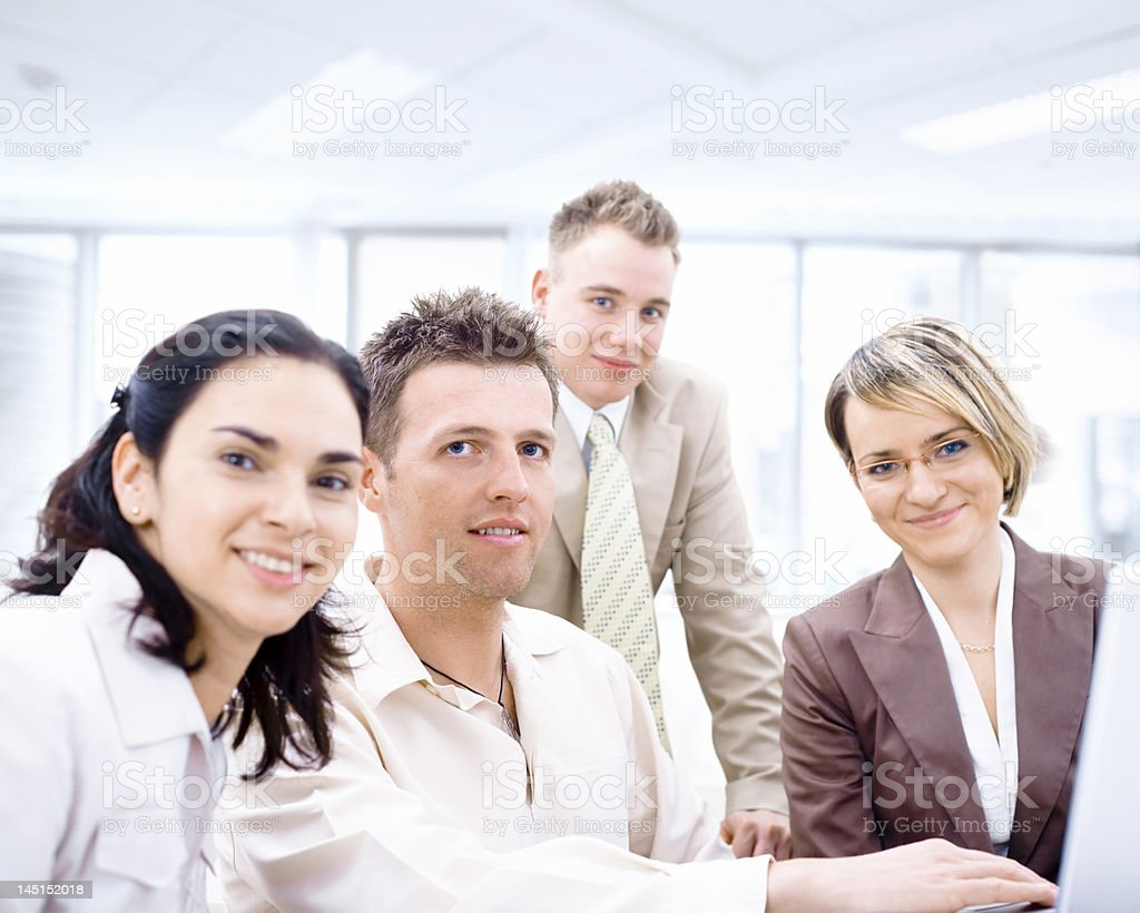 Group of four smiling business people working together royalty-free stock photo
