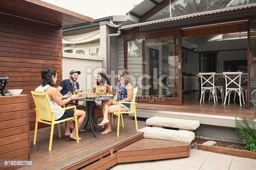 istock Group of four young adults relaxing on patio outside house with food and drink 916595296