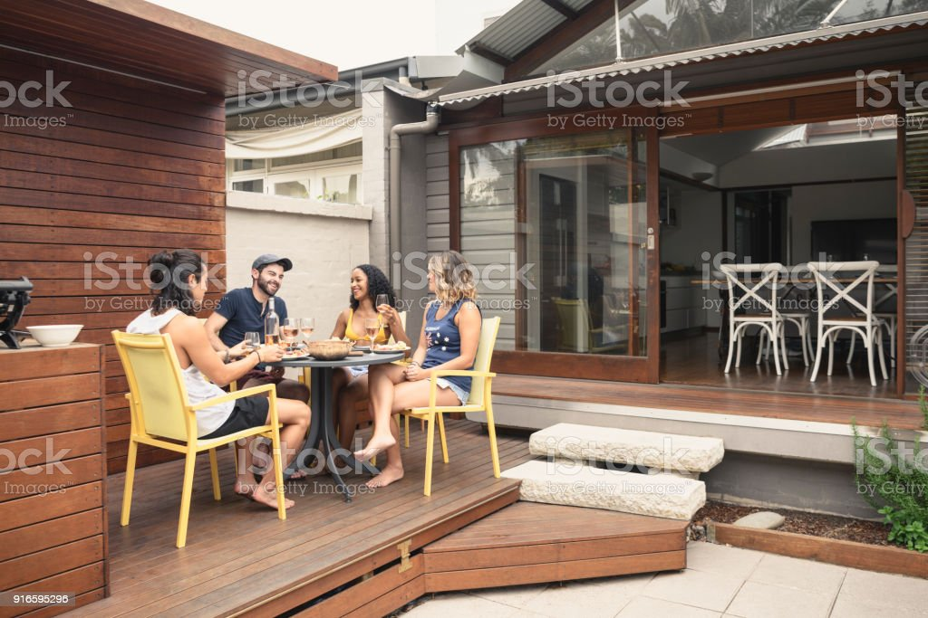 Group of four young adults relaxing on patio outside house with food and drink stock photo