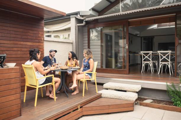食べ物や飲み物を家の外のパティオでリラックスできる 4 つの若い大人のグループ - デッキ ストックフォトと画像