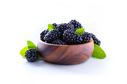 Front view of a wooden bowl full of blackberries with some mint leaves isolated on white background. Studio shot taken with Canon EOS 6D Mark II and Canon EF 100 mm f/ 2.8