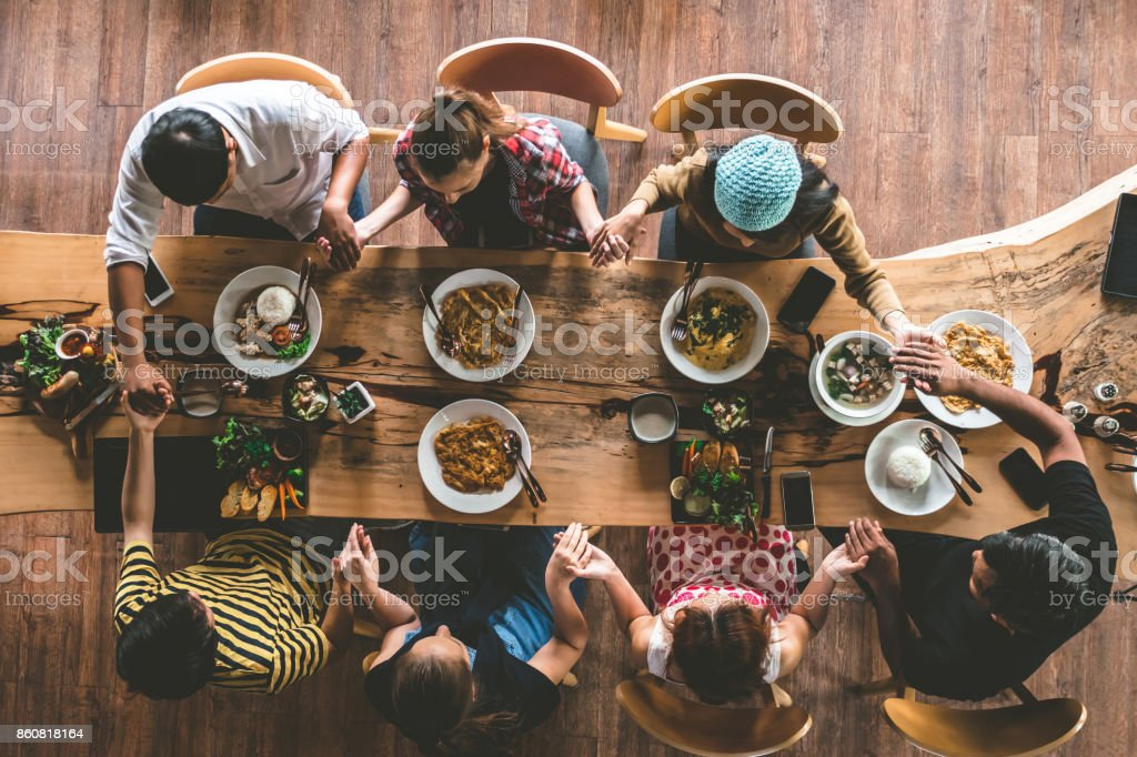 Group of friend pray before having nice food and drinks, enjoying the party and communication, Top view of Family gathering together at home for eating dinner. stock photo