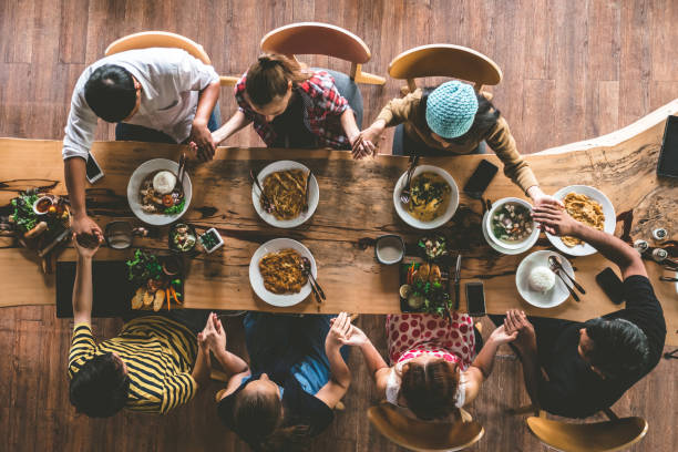 group of friend pray before having nice food and drinks, enjoying the party and communication, top view of family gathering together at home for eating dinner. - easter brunch stock photos and pictures
