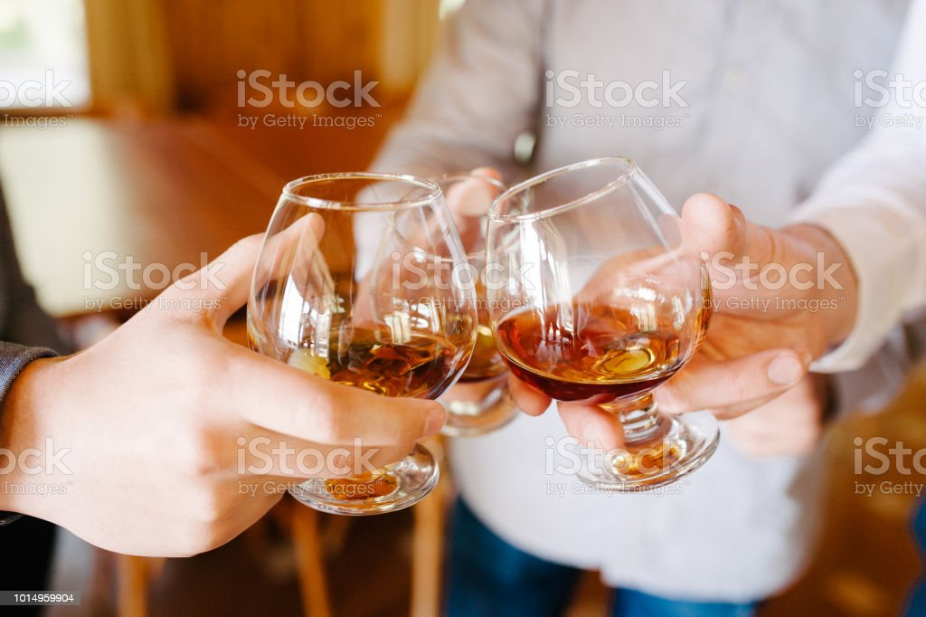 Group of friends a toast to the cheers of cognac or brandy stock photo