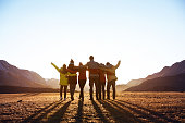 Group of happy friends stands and hugs against sunset mountains