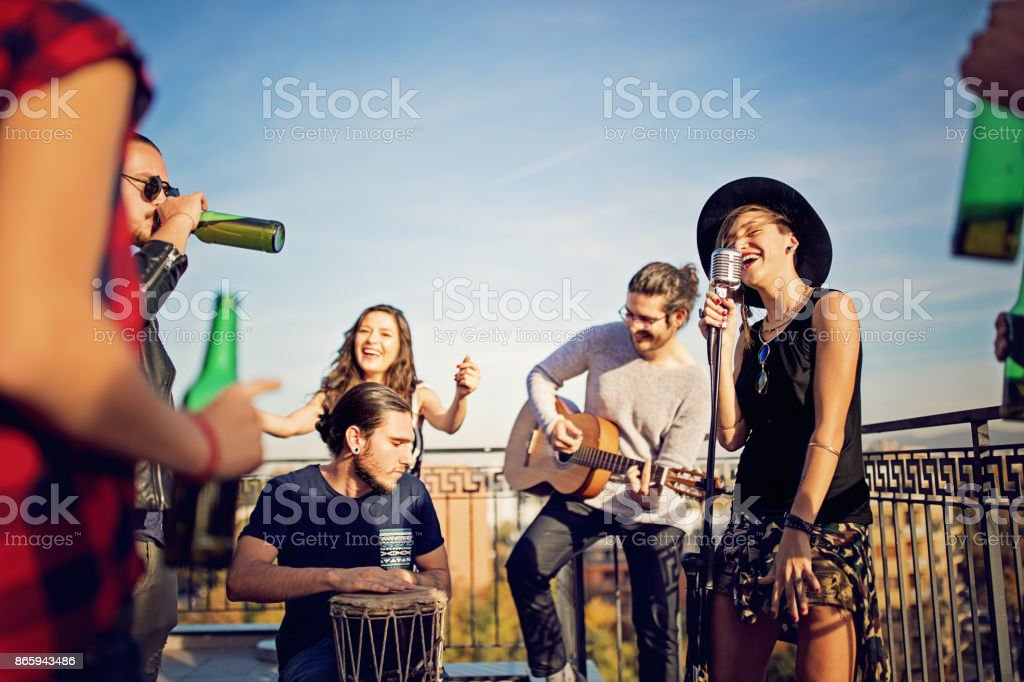 Group of friends are celebrating with a concert on the roof terrace stock photo