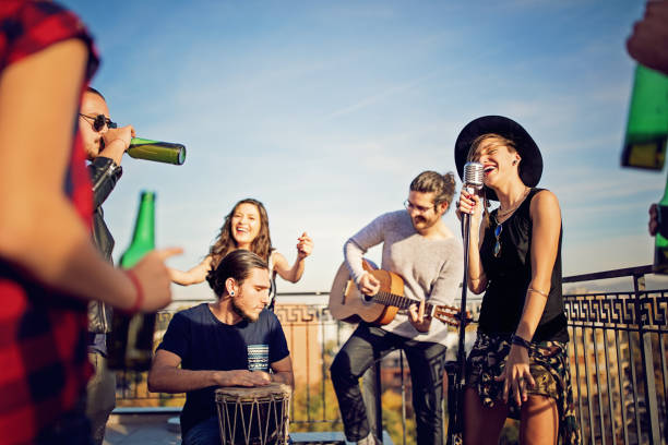 group of friends are celebrating with a concert on the roof terrace - performance group stock photos and pictures