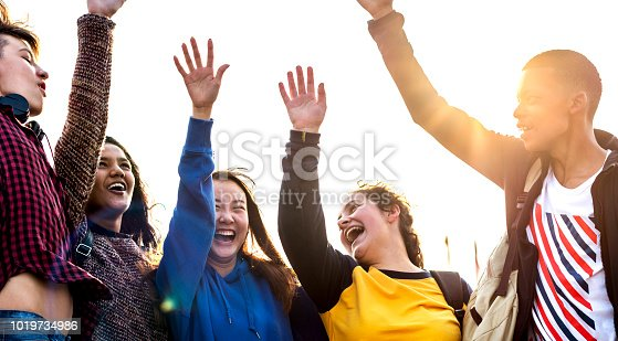 Group of friends arms raised together support and teamwork concept