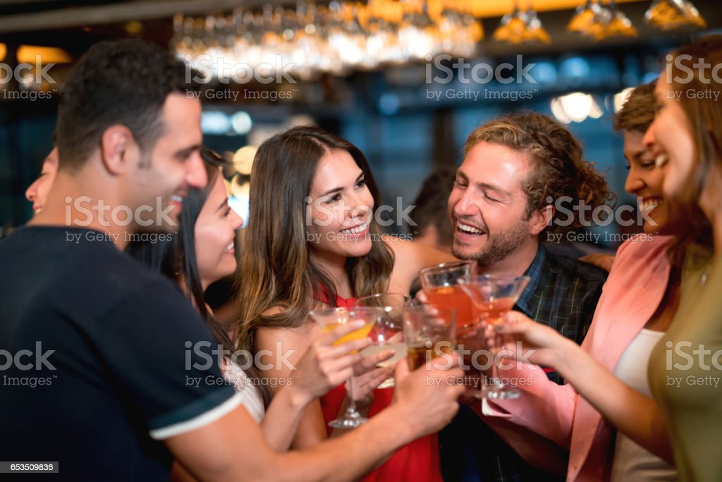 Group of friends at a bar making a toast stock photo