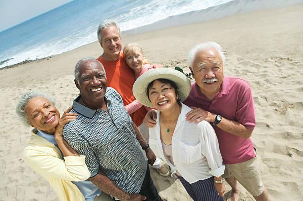 group of friends at beach - 50 59 jaar stockfoto's en -beelden