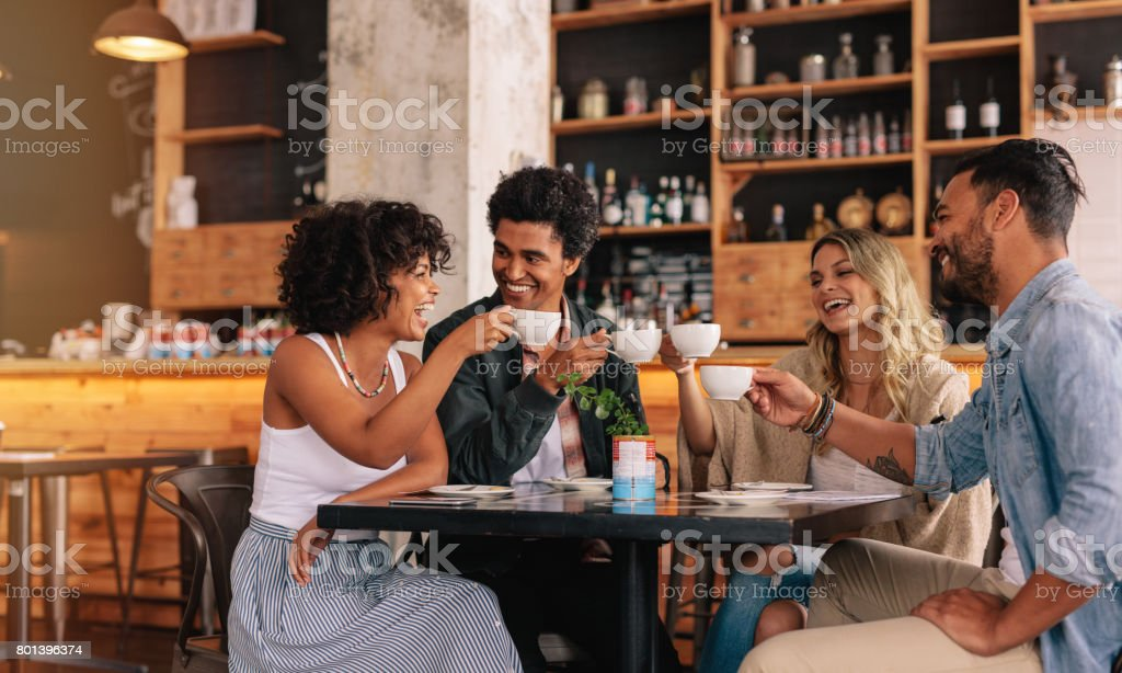 Group of friends at cafe having coffee together Young people sitting at cafe table and having coffee together. Group of friends making a toast with coffee. Adult Stock Photo